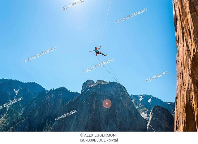 Person swinging mid air against blue sky on alcove swing at the base of El Capitan, Yosemite Valley, California, USA
