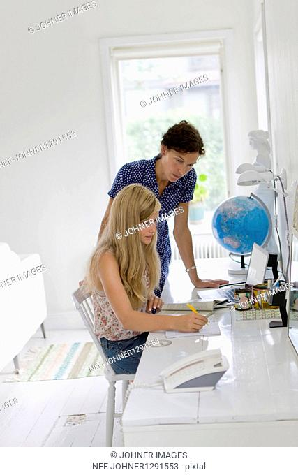 Mother assisting her daughter doing homework