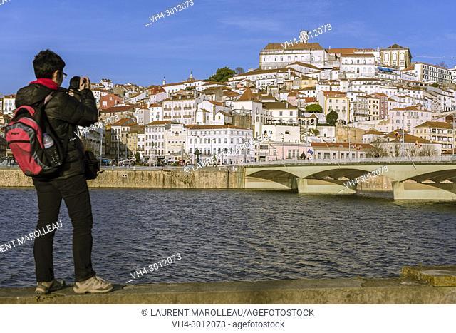 Woman Taking a picture of the University Town of Coimbra with Mondego River and Santa Clara Bridge. Coimbra, Baixo Mondego, Centro Region, Portugal, Europe