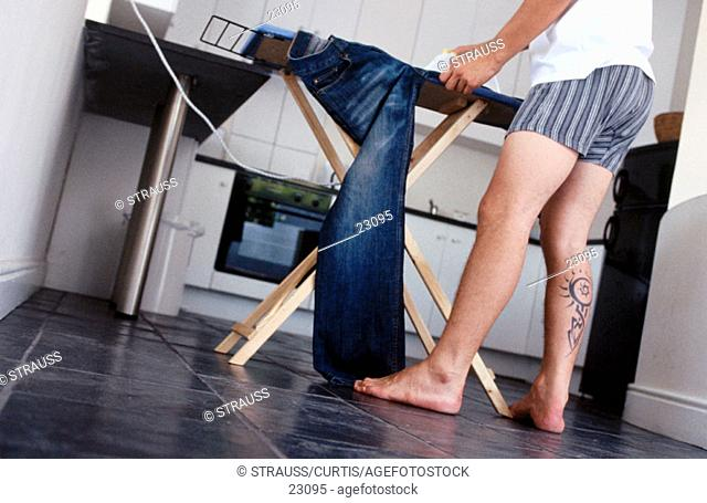Young man with tattoo ironing his jeans