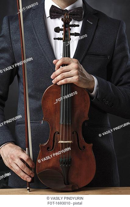 Midsection of violinist holding violin at table against black background