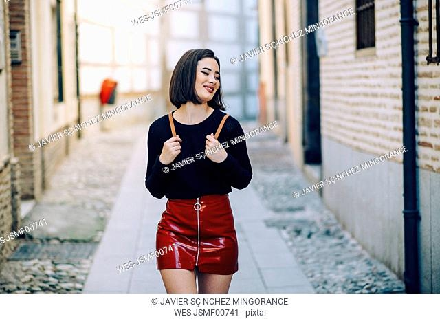Portrait of young woman wearing red patent leather skirt with zipper