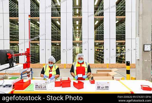 26 June 2020, Saxony, Leipzig: DHL employees pack e-cigarettes in a logistics centre jointly operated by DHL and Philip Morris Germany