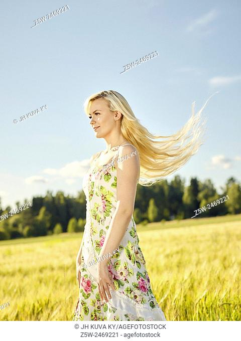 Beautiful fair skin blonde wearing a floral dress, summer sunlight, barley field on background