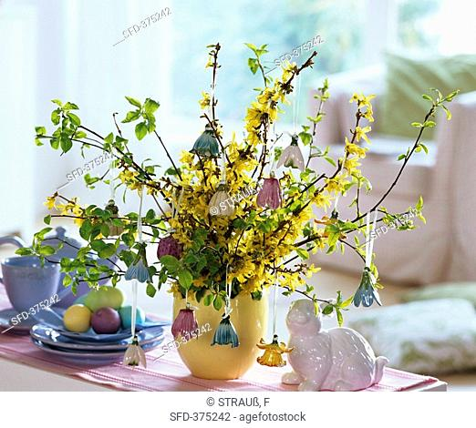 Vase of forsythia and bird cherry with porcelain bells