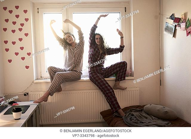 two young women in pyjamas sitting at windowsill in shared student apartment