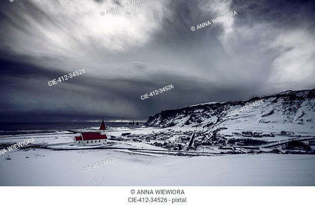 Church in remote snow covered landscape below stormy sky, Vik, Iceland