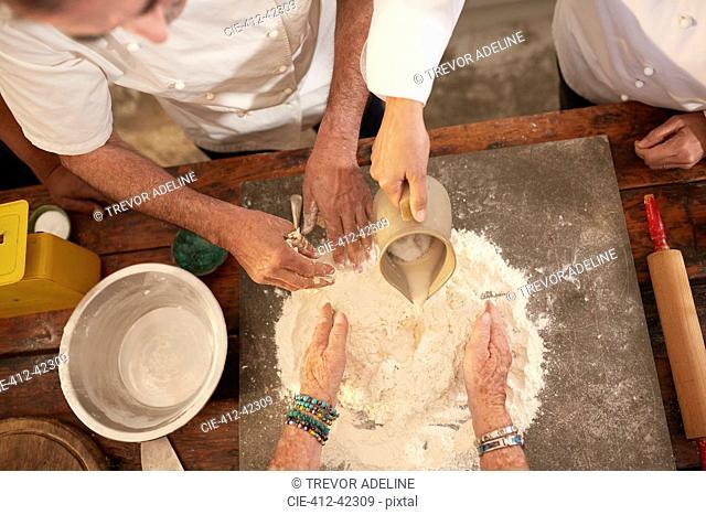 Overhead view chefs making pizza dough flour nest