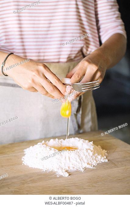Woman preparing pasta dough, flour and eggs