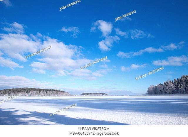 Wintry view of the horizon with fresh colors, white ice of the lake and clear blue sky