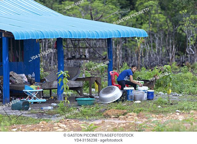 Woman washing clothes at the door of her houseKoh, Rong Island, Sihanoukville province, Kingdon of Cambodia