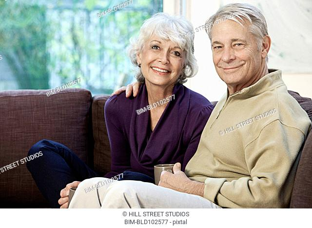 Caucasian couple sitting together on sofa