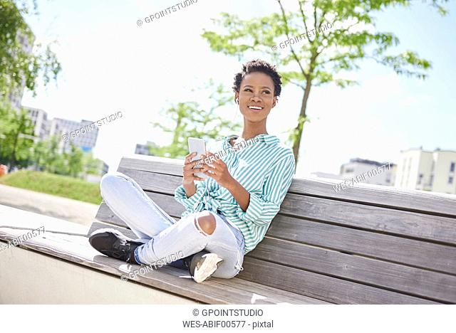 Portrait of smiling young woman with cell phone and earphones sitting on bench