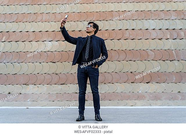 Fashionable young businessman taking selfie with mobile phone