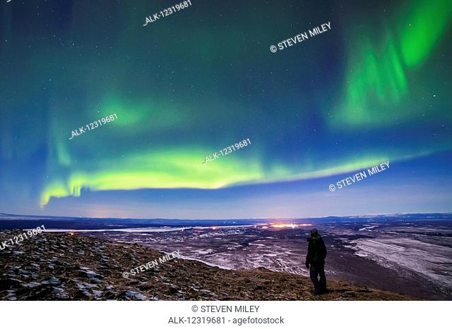 A man observes the aurora borealis from the top of Donnelly Dome south of Fort Greely and Delta Junction, the lights of which are seen glowing in the distance