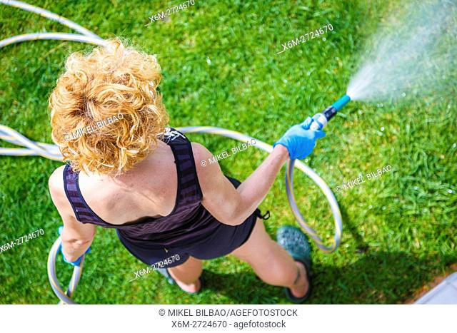 Woman irrigating a garden