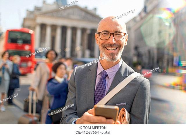 Portrait smiling, confident businessman texting with cell phone on urban city street, London, UK