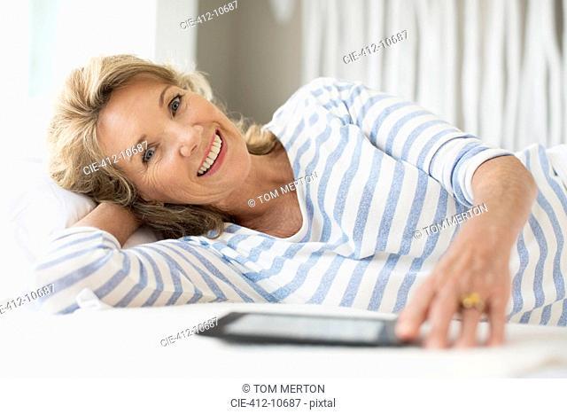 Older woman using digital tablet on bed