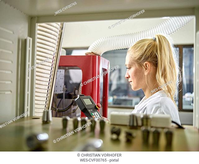 Female technician maintaining CNC machine