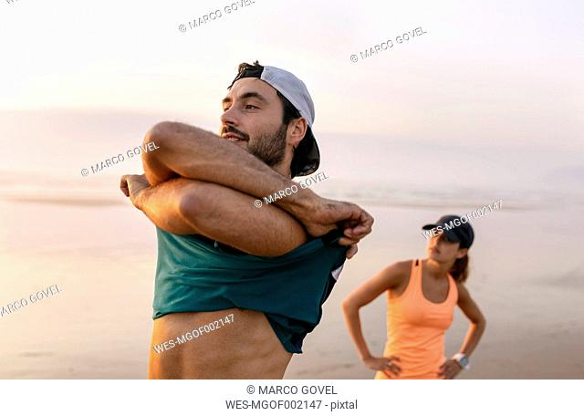 Athletes couple training on the beach in the evening, man undressing t-shirt