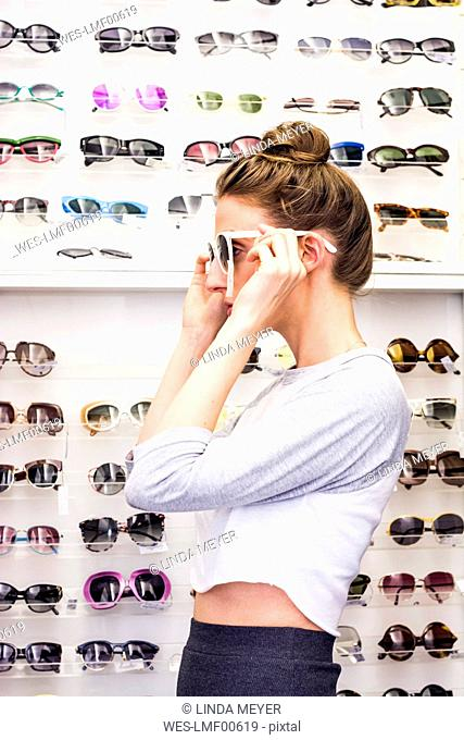 Young woman putting on sunglasses in an optician shop