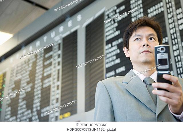 Close-up of a businessman at an airport holding a mobile phone
