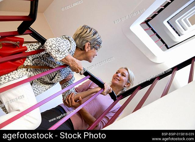 Elderly woman being helped by another woman to climb the stairs