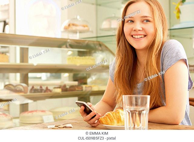 Girl in cafe holding smartphone smiling