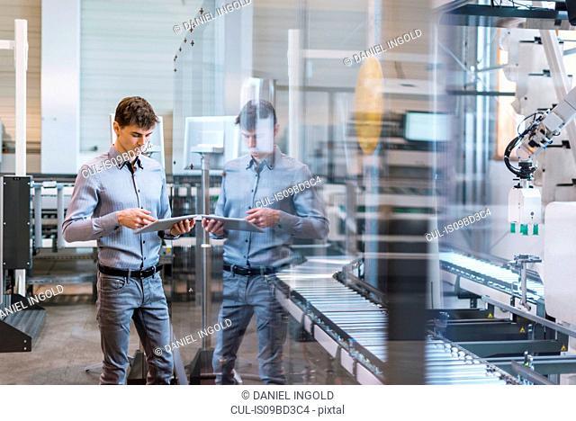 Young man in factory, beside conveyor belt, using digital tablet