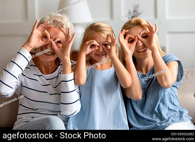 Multigenerational women sit on couch fooling around do funny faces making binoculars with fingers like glasses shapes pose for camera