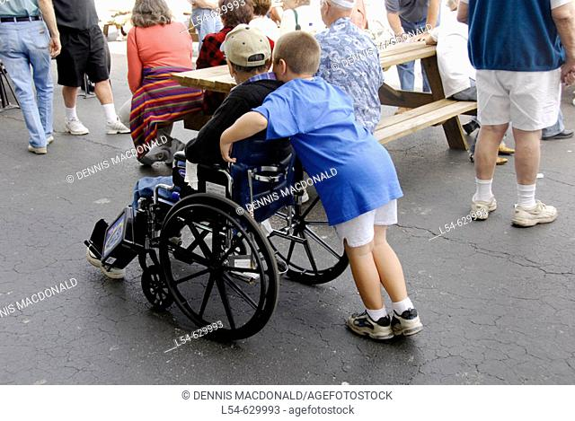 Grandson pushes grandfather in a wheelchair