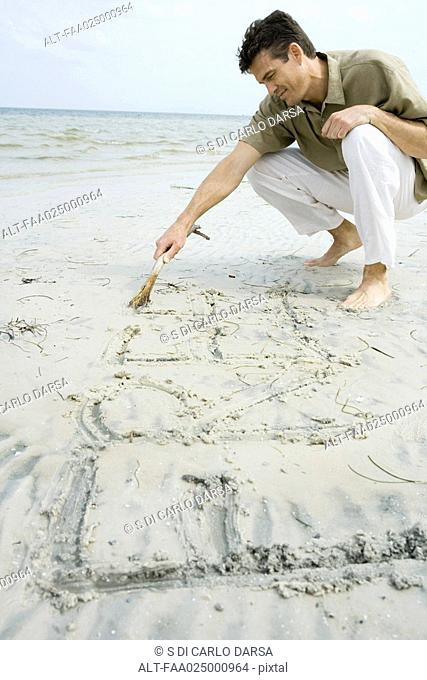 Barefoot man writing word 'free' on beach with stick