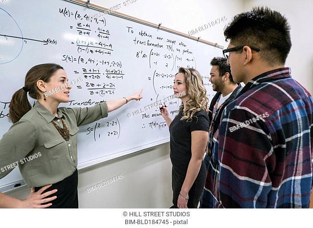 Professor helping students in college classroom