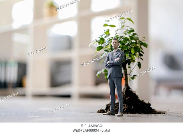 Businessman figurine standing next to a little tree