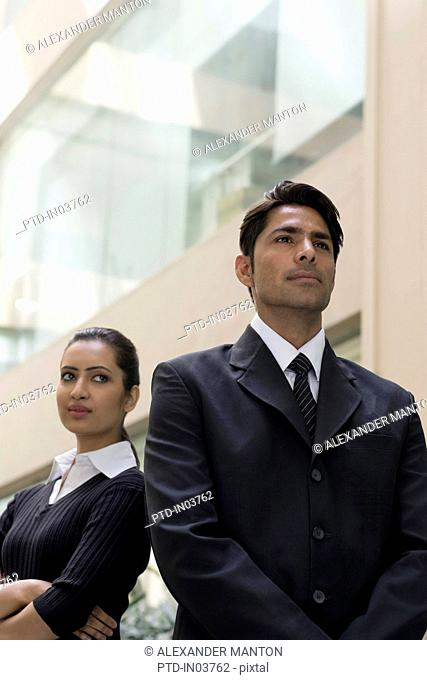 Businesswoman looking at businessman standing in front of her