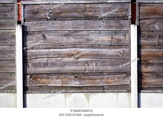A close up section of horizontal, overlap wooden garden fence in brown. Manchester