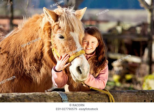 Happy little girl with a delightful smile standing in the sunshine cuddling her horse
