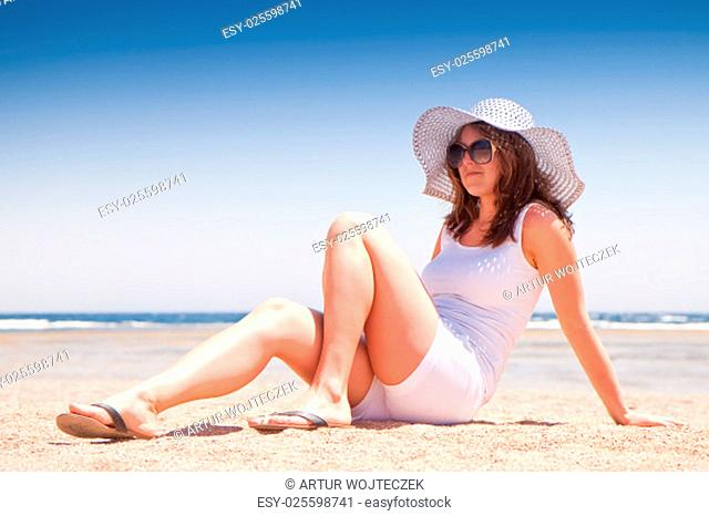 young girl sitting on the sand at the beach
