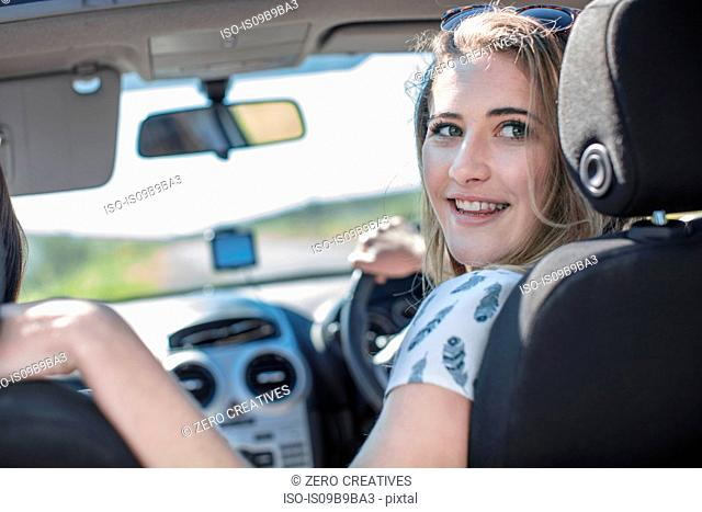 Young woman driving car, looking over shoulder, smiling