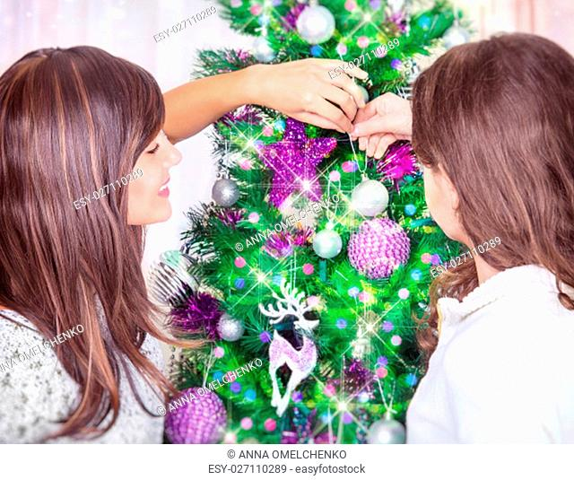 Closeup photo of a mother and teen daughter decorating beautiful big Christmas tree at home, having fun together, spending winter holidays in family house