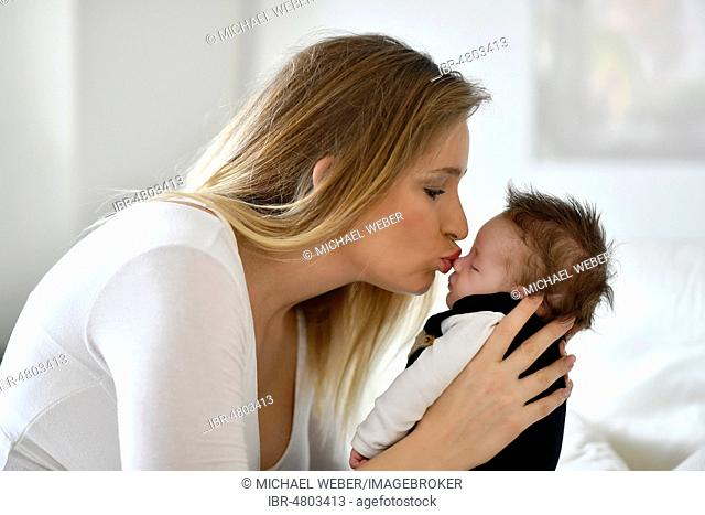 Mother kissing baby, 4 weeks, Baden-Württemberg, Germany