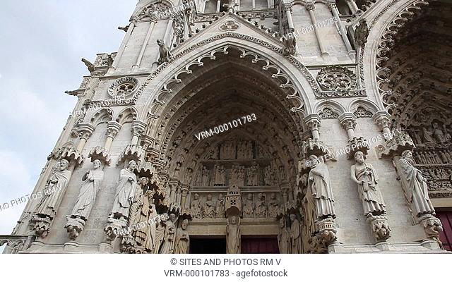 CU, TILT up, PAN, daylight, exterior: view of the west facade, the left portal - Portal of St. Firmin the Martyr. The Cathedral is in the High Gothic or...
