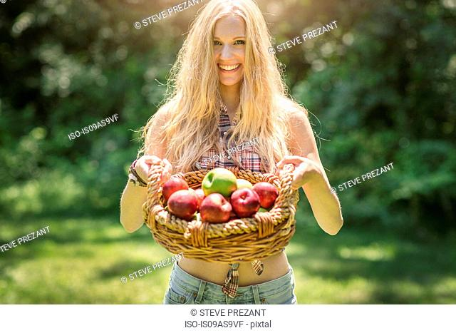 Portrait of young woman holding up basket of fresh apples in garden