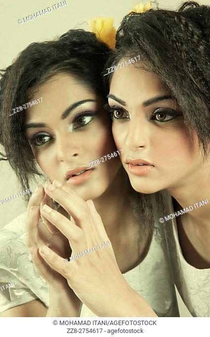 Beautiful young woman leaning on a mirror
