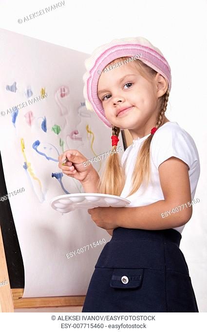 Four-year-old girl playing in the artist and draws on the easel painting. In the arms of children brush and palette