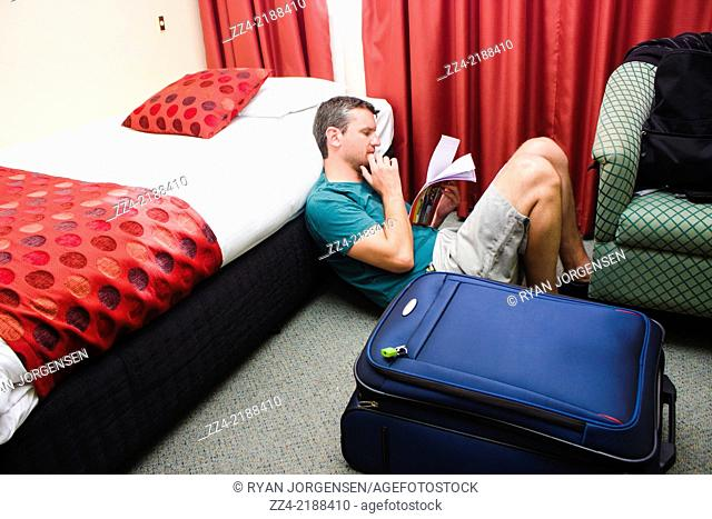 Travelling man holding travel itinerary in hotel accommodation when planning holiday sightseeing activities