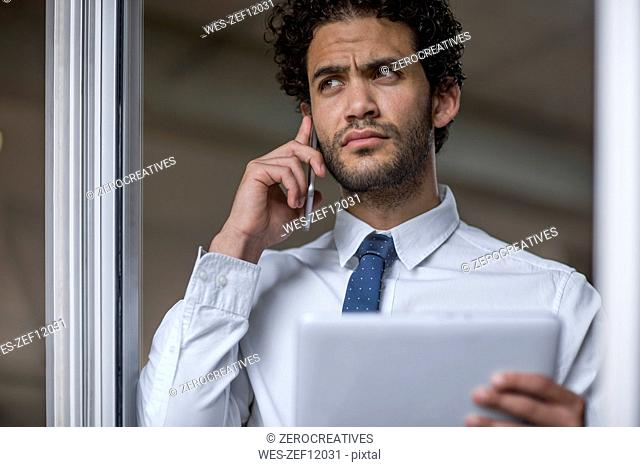 Businessman with cell phone and tablet looking out of window