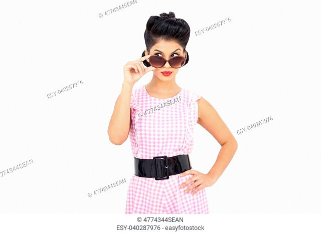 Playful black hair model looking over her sunglasses on white background