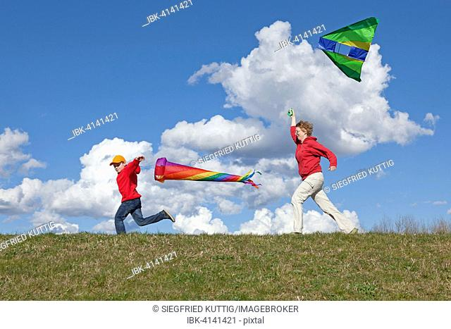 Mother and son flying a kite and a windsock, Germany