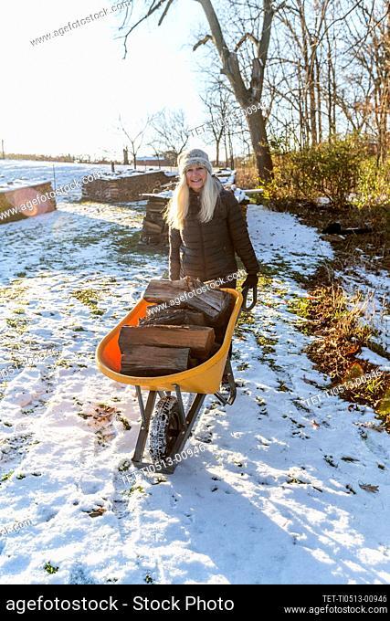 Woman holding wheelbarrow with logs in snow